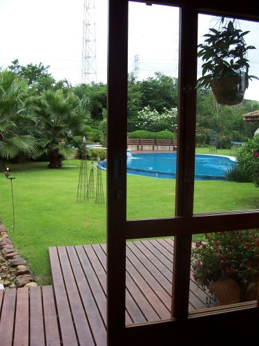 Vista do jardim com a piscina a partir do gazebo. Bem prximo  porta, o vaso de cermica com camaro-vermelho (Justicia brandegeana). Ao fundo, em um horizonte de diversos volumes e texturas verdes, destaque para a bela resed de flor branca (Lagerstroemia indica) e a escultura de clsia (Clusia fluminensis)