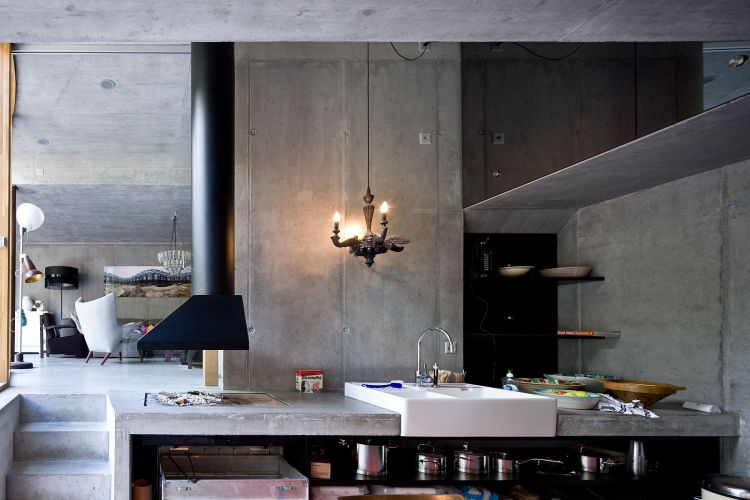 Com ambientes integrados, a Villa Vals é um exemplo do estilo contemporâneo de morar. Na foto, detalhe em primeiro plano da cozinha e sala de jantar e, um lance de degraus acima, a sala de estar. A luminária pendente sobre a pia é assinada por Maarten Baas