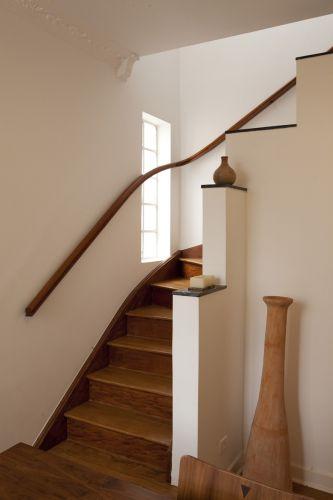 Escada com revestimento de madeira e corrimão curvo de madeira, do sobrado em Pinheiros, reformado pela arquiteta Ana Sawaia