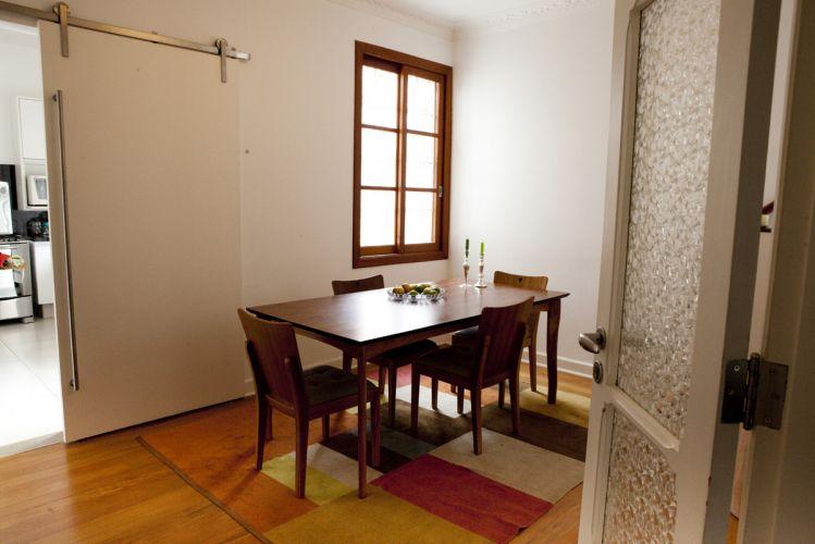 Sala de jantar do sobrado em Pinheiros, reformado pela arquiteta Ana Sawaia. O assoalho de madeira foi restaurado e foi instalada uma porta de correr no acesso à cozinha