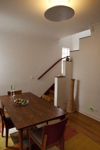 Sala de jantar do sobrado em Pinheiros, reformado pela arquiteta Ana Sawaia. A escada e o assoalho de madeira foram restaurados