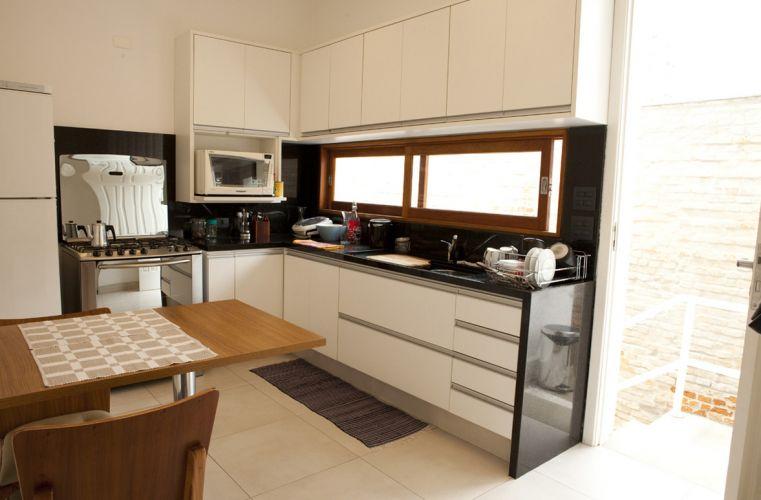 Cozinha com piso porcelanato (Porto Bello Bauhaus 60 x 60 cm) e armários, da Cidlar Móveis Planejados, em mdf branco texturizado. As bancada e os frontões são em granito preto são gabriel. A mesa parafusada na parede tem pé de alumínio e é feita de madeira revestida com fórmica, da Cidlar Móveis Planejados