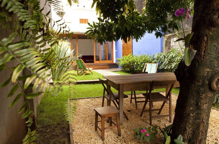 Jardim nos fundos da casa com projeto de reforma da arquiteta Ana Sawaia. Foram usadas grama esmeralda e amendoim, além de gardênias e fórmios. Junto ao anexo foi definido um espaço para refeições ao ar livre, sobre uma caixa revestida com pedriscos
