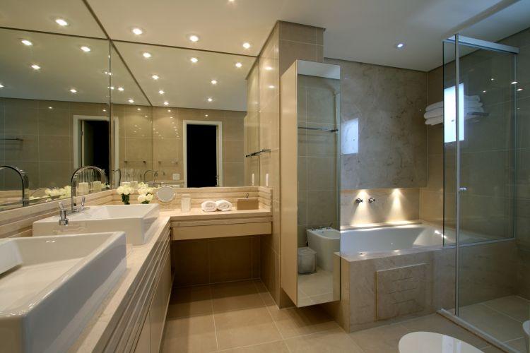 O banheiro da suíte máster tem a bancada de mármore crema marfil com duas cubas da Deca; à direita, a banheira de hidromassagem embutida no boxe