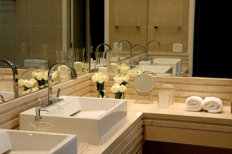 Detalhe da bancada do banheiro da suíte principal, com bancada de mármore do tipo crema marfil e cubas da Deca