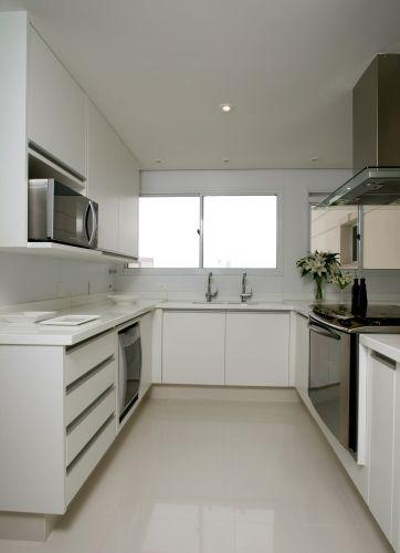 Totalmente branca, a cozinha se diferencia do restante do apartamento, onde predominam os tons de bege e marrom. O ambiente tem piso revestido com porcelanato Portinari, modelo Diamante Polido, bancada em Marmoglass e armários com acabamento laminado da Florense