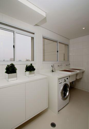 A área de serviço acompanha o branco da cozinha e tem mobiliário revestido com material laminado da Florense