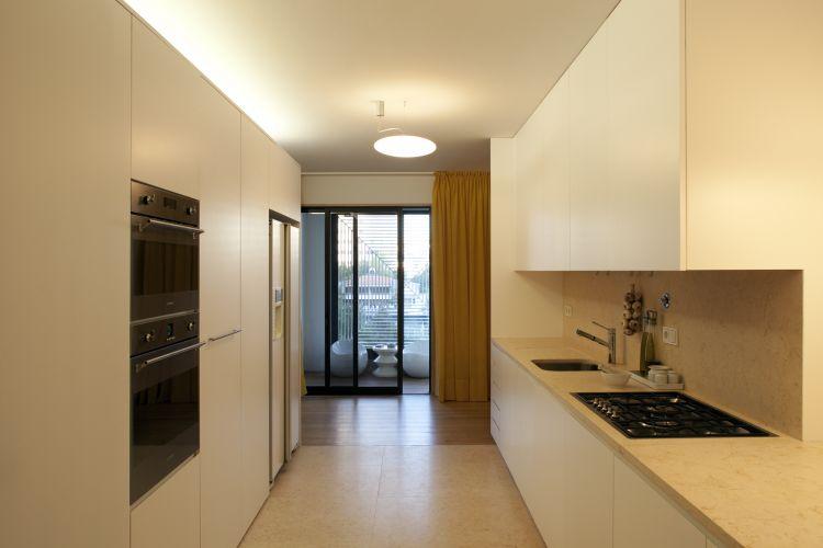 Esta vista da cozinha mostra, ao fundo, a varanda fechada que serve também à sala de jantar. Aqui também foram usadas cortinas amarelas para ocultar as esquadrias que desagradam os moradores