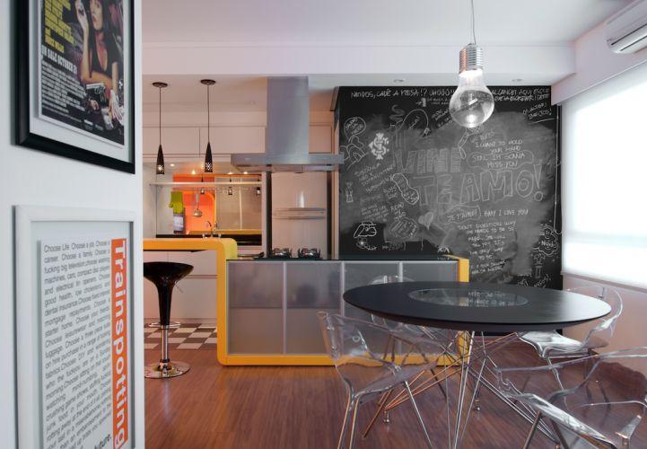 No primeiro plano, a mesa de jantar cujo tampo lembra um disco de vinil. Ao fundo, separando a lavanderia do espaço de jantar, a caixa de gesso pintada de esmalte sintético fosco preto da Suvinil, usada como lousa para brincadeiras e recados