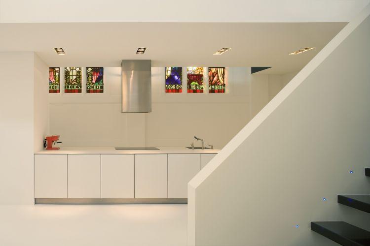 Inusitado é ter vitrais sacros na cozinha: os revestimentos, muito lisos e brancos, acompanham a proposta limpa de decoração, quase etérea, que quando não é diretamente composta por metal e madeira, traz grandes áreas em elementos laminados. Igreja transformada em residência por Zecc Architecten, na Holanda