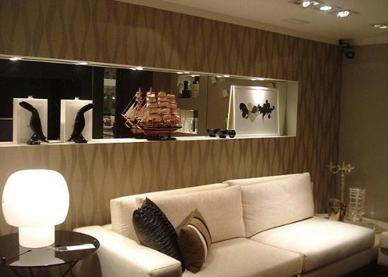 A parede da sala de estar ganhou ritmo com a sinuosidade das faixas do papel de parede Suede da Celina Dias