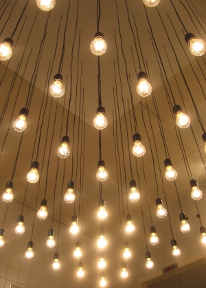 Projeto de iluminação composto por várias lâmpadas incandescentes pendentes do forro, aplicado em um hall