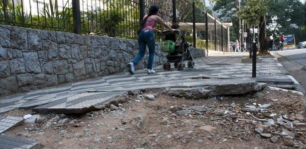Nesta foto de 2010, pedestre caminha por calçada em mau estado de conservação em avenida de SP