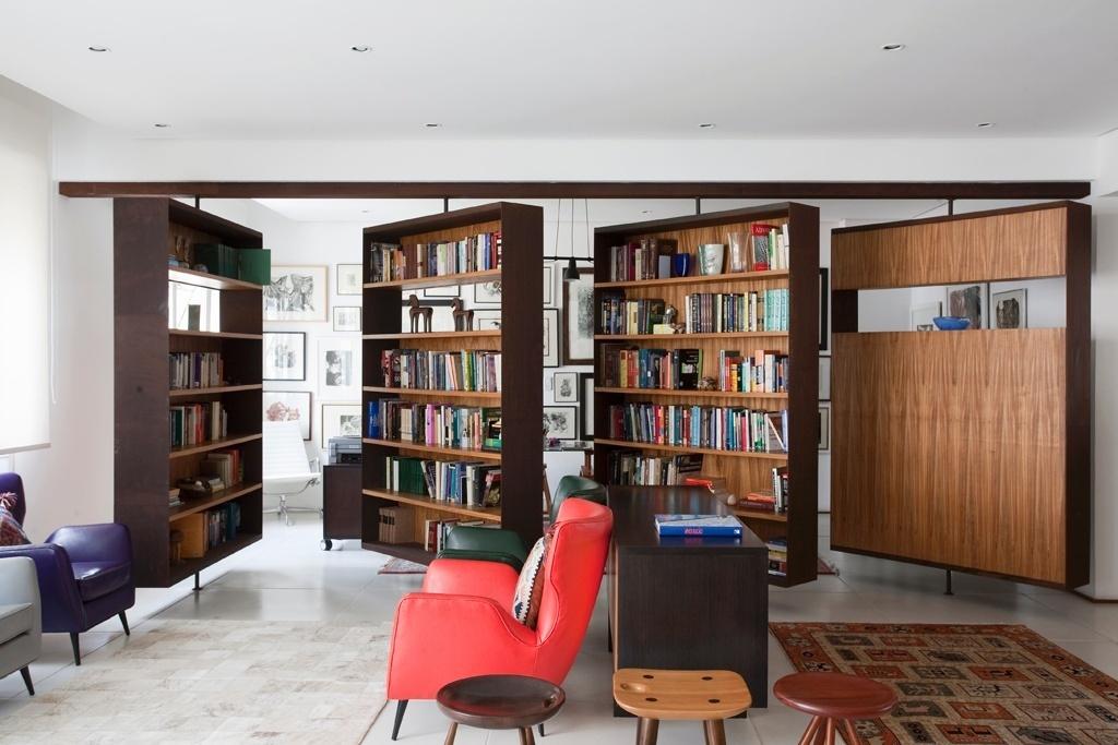 Estar e escritórios separados por estantes pivotantes em apartamento reformado pelo escritório FGMF