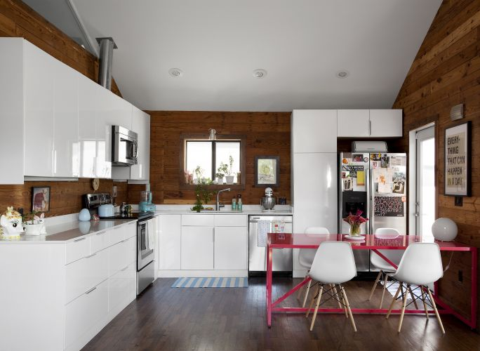 A cozinha do chalé dos anos de 1930, existente no terreno onde foi construído o conjunto residencial SOL, em Austin, no Texas. Incorporado a uma nova casa, o chalé manteve a parede original de pinho e o piso de carvalho. O mobiliário é da Ikea