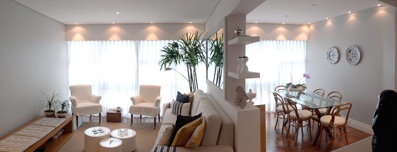 O espelho aplicado no pilar que separa os ambientes do living amplia a sala de estar e a iluminação. Quando as cortinas estão abertas, o espelho reflete a imagem da Lagoa Rodrigo de Freitas, vista através da fachada envidraçada