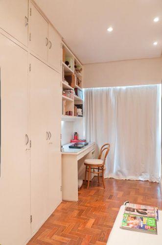 A planta do quarto do casal forma um L, cujo trecho mais estreito foi transformado em escritório, com prateleiras e escrivaninha executadas em MDF com acabamento de laca branca