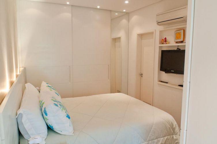 O canto da parede junto à porta do dormitório foi aproveitado para a fixação de um espelho com altura igual ao do pé-direito do apartamento; um nicho em marcenaria recebeu a TV de plasma