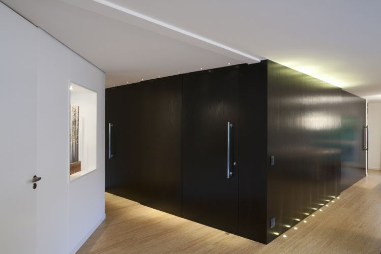 O volume de MDF revestido com lâmina de madeira ebanizada funciona como um elemento escultórico do social