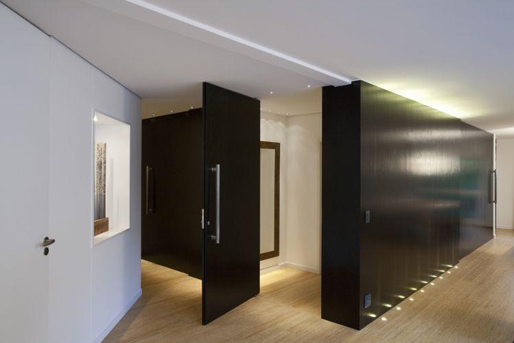 O volume de MDF revestido com lâmina de madeira ebanizada dá forma a porta de entrada pivotante