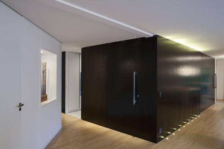O volume de MDF revestido com lâmina de madeira ebanizada dá forma a porta de correr que abre-se para a galeria
