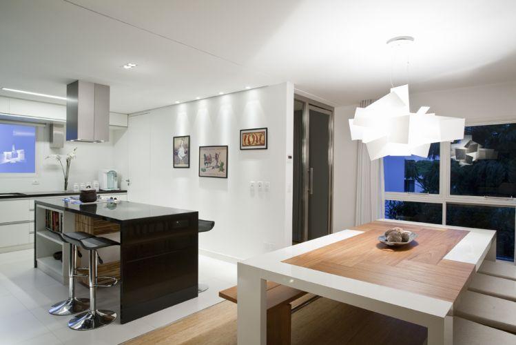 O piso de porcelanato simplesmente branco da Portobello delimita o ambiente da cozinha. A adega confeccionada por Janos Biezok tem porta em aço inox da Wood & Steel