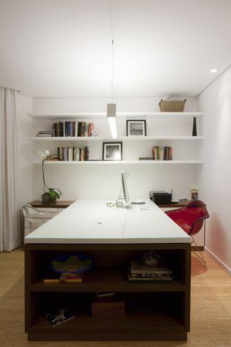 No escritório, bancada de madeira com tampo de vidro pintado e estantes, executados pela Marcenaria Ernando. O pendente com iluminação mista é da Lumini