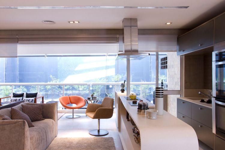 A bancada de corian, projetada pela arquiteta responsável pelo projeto, divide o estar da cozinha. Ela abriga objetos decorativos nas prateleiras e sustenta o cooktop, além de servir como área de trabalho para quem está cozinhando