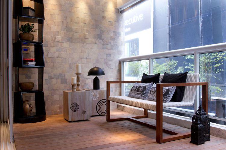 Revestida com deck de madeira cumaru e pedra ônix, a varanda é um espaço de relaxamento e social. Sofá de madeira e tela da Arredamento/Manufatura e mesas de madeira e estante da Breton Actual