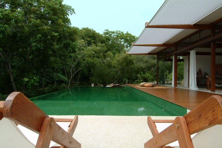 Vista da piscina a partir do solário. Ao fundo, a área reservada para pendurar redes é integrada à área de preservação permanente. A varanda é protegida da insolação direta pelo toldo de poliéster reforçado e microperfurado (da Soltis)