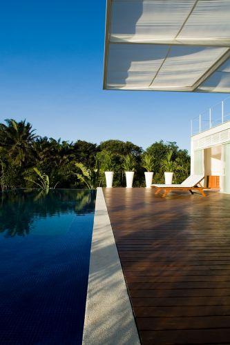 Alinhada à fachada norte, a piscina com borda infinita e, ao fundo, a área de preservação ambiental. A grande cobertura de estrutura metálica e tecido se projeta sobre o deck de madeira. A casa projetada pela arquiteto paulista André Luque fica em Camaçari, na Bahia