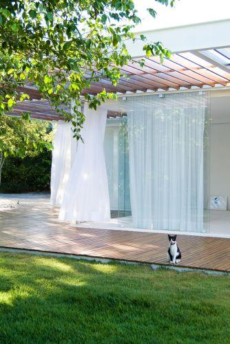 O pergolado de cumaru protege a casa da insolação, enquanto as grandes portas de correr em vidro garantem a boa ventilação