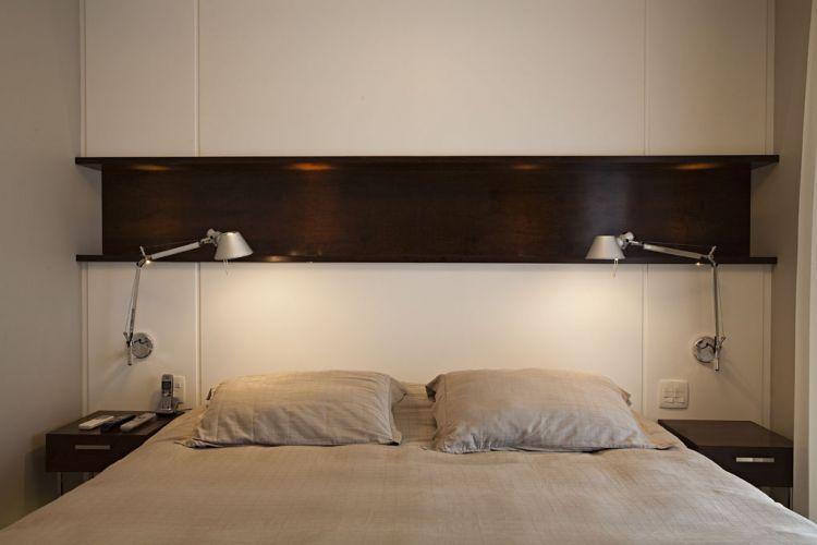 Na suíte principal, a cabeceira da cama é um painel de madeira com acabamento em laca branca e cortado de fora a fora por um nicho de imbuia. As luminárias são da La Lamp