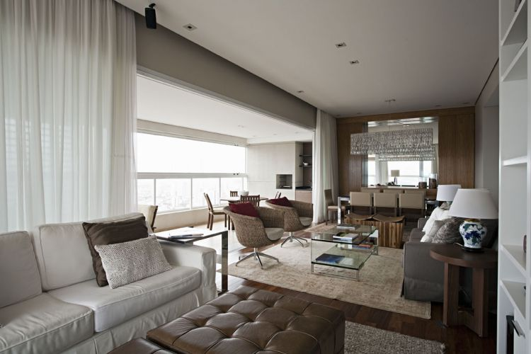 A foto evidencia a integração ente os ambientes que formam o living e a varanda, em L, com churrasqueira. Giratórias, as poltronas da sala de estar, da Artefacto, servem tanto à sala de estar quanto à varanda