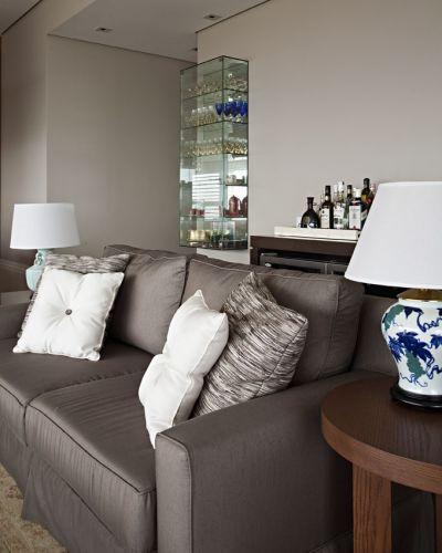 Em primeiro plano, o sofá da Ideia Básica com almofadas da Empório Beraldin. As mesas laterais são da Artefacto e, os abajures, da Vila Vitória. Ao fundo, a cristaleira desenhada por Andréa Parreira e executado pela Casa dos Vidros