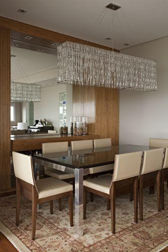No ambiente de jantar, o móvel de freijó que acomoda o espelho (da Casa dos Vidros) é formado por dois armários laterais e um aparador. O trabalho de marcenaria foi executado pela Detalhe e Entalhe. A mesa é da Breton e o lustre é da Scatto