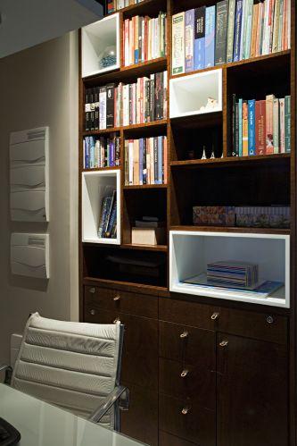 No escritório foi instalada uma estante embutida de imbuia com alguns nichos com acabamento de laca branca. Trabalho da marcenaria Detalhe e Entalhe. Do lado do móvel aparecem os quadros gerais de luz do apartamento