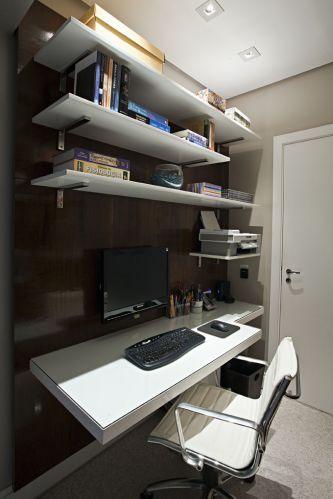 Suspensa, a mesa do computador tem acabamento de laca branca, assim como as prateleiras, que foram instaladas em um painel de imbuia. Trabalho de marcenaria da Detalhe e Entalhe