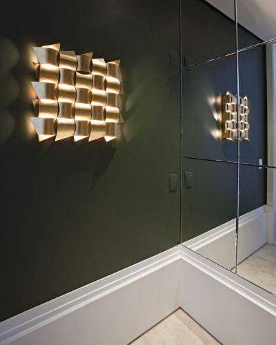 Detalhe do hall do elevador destaca a luminária de metal revestida com folhas de ouro da Scatto
