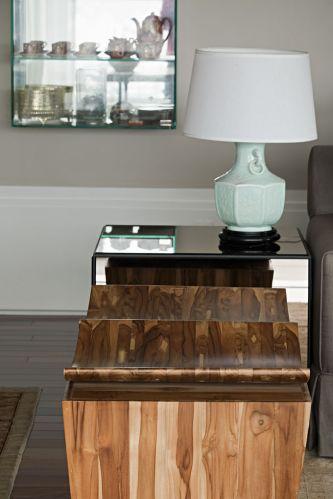 No detalhe do estar, aparecem em primeiro plano os bancos de madeira de reflorestamento da Gallery. A mesinha lateral é da Artefacto e o abajur, com base de louça e cúpula de tecido, é da Vila Vitória