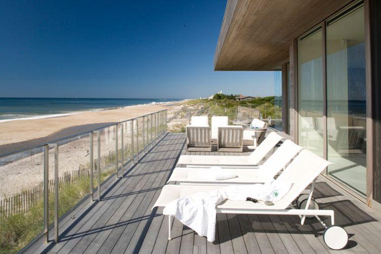 O terraço junto à fachada frontal da casa é um prolongamento do deck da piscina. O guarda-corpo incolor e transparente permite a vista quase sem obstrução da praia e do mar