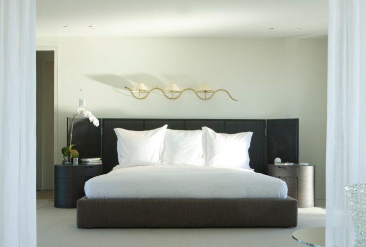 Na suíte principal, as cores claras aplicadas ao piso e às paredes destacam a cama cinza chumbo. Na foto, o quarto é visto a partir da saleta de onde se tem acesso ao terraço