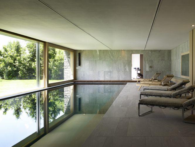 Nos revestimentos da área de piscina coberta, mais pedras. O fechamento com vidro, no entanto, pode ser aberto; e toda a área social da casa fica integrada ao jardim