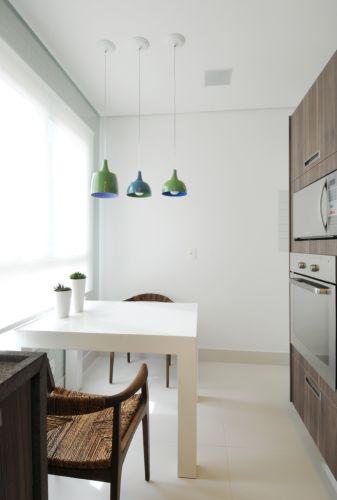 Sobre a mesa laqueada executada em marcenaria, o trio de pendentes coloridos da Bertolucci. O apartamento de 150 m² no Cambuí, em Campinas (SP), tem decoração assinada pela arquiteta Elaine Carvalho