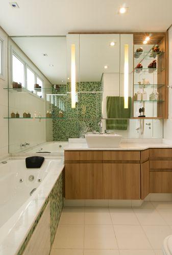 No banheiro de 6 m² ligado ao quarto de casal, criado pelo arquiteto Samy Dayan e o designer de interiores Ricky Dayan, o revestimento em laminado madeirado contrapõe com as pastilhas de vidro da banheira que se repetem no box, integrando as duas áreas. Repare na iluminação embutida no espelho que facilita a feitura da barba ou da maquiagem. A lâmpada utilizada é a fluorescente convencional, garantindo claridade discreta e delicada