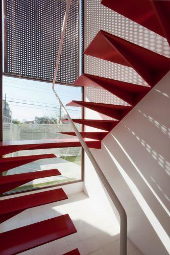 Detalhe da escada metálica vista por dentro. Escultórica, com acabamento em pintura epóxi vermelha, conta com um discreto corrimão branco para segurança. O sombreamento é feito pelo painel de muxarabi
