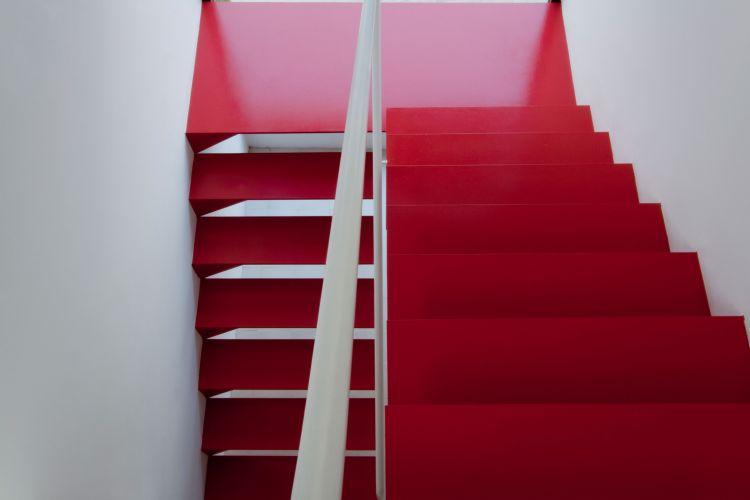 O acesso à casa passa obrigatoriamente pela escada vermelha. Sem grandes complicações de execução, é o elemento que reafirma a qualidade do projeto