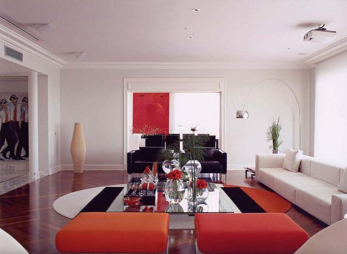 Molduras nos vãos das portas, rodatetos e colunas conferem o desenho clássico ao estar. Em linhas retas e cores neutras, os móveis da Atrium proporcionam aconchego. Como contraponto, dois pufes cor de laranja compõem com o tapete da Santa Mônica, idealizado pela arquiteta no mesmo tom de laranja conforme solicitação de Amaury Jr. Ao centro, a mesa envidraçada reflete luz. Nas aberturas, a persiana da Luxaflex filtra os raios solares e permite a realização de sessões de vídeo