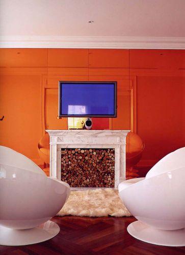O projeto previu revestimento de espelho tonalizado de laranja (com película Saflex, da Santa Marina Vitrage by Penha Vidros), que ressalta o frontão de mármore de Carrara da lareira. As cadeiras futuristas da Brentwood demarcam o uso da TV de plasma fixa no painel. Para completar com conforto, o tapete que remete à pele de um urso macio bem à frente