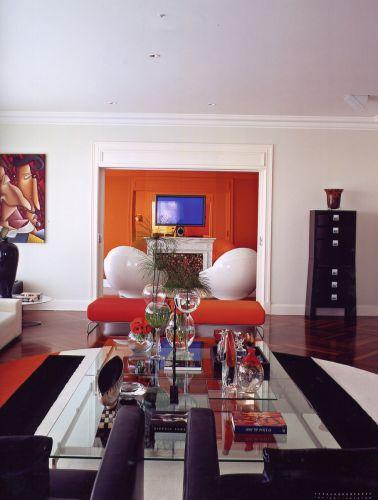 O living se relaciona à sala de TV pelo vão e também pela cor laranja, a preferida de Amaury, sempre combinada com o branco